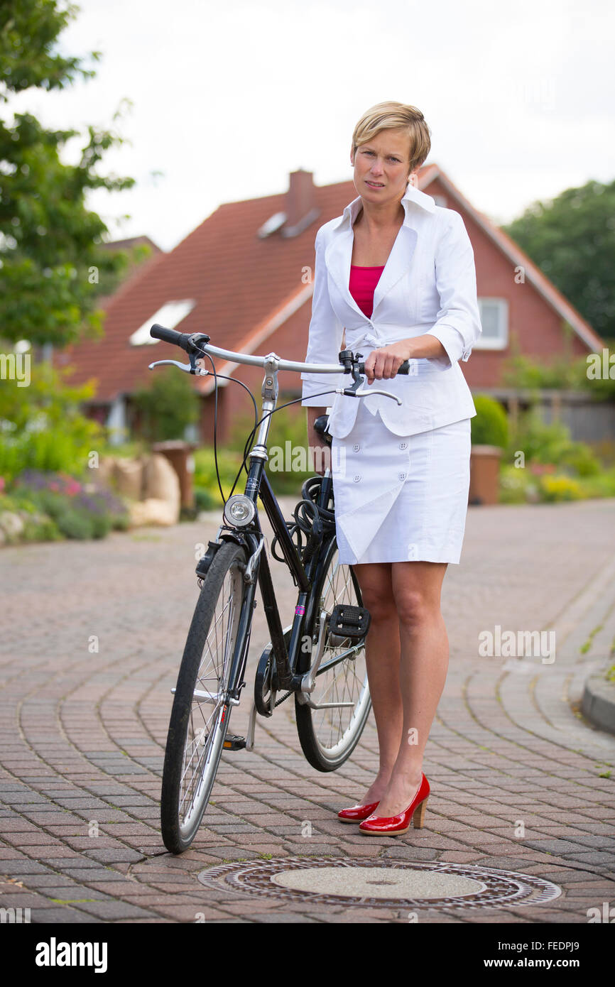 Woman with business costume has a flat tire and pushing her bike - Stock Image