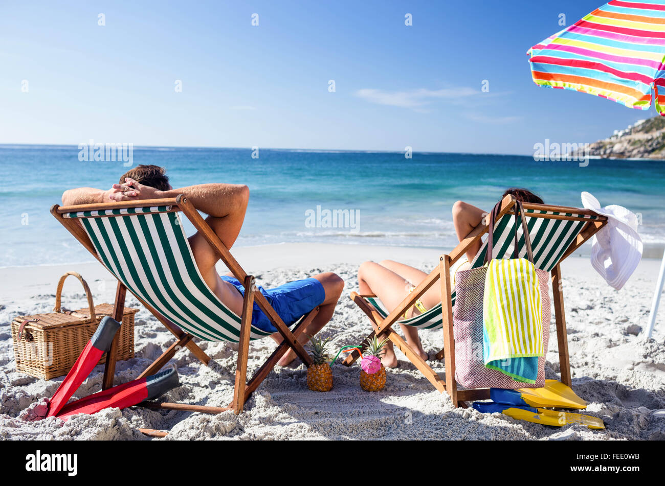 Cute couple lying on deckchairs Stock Photo