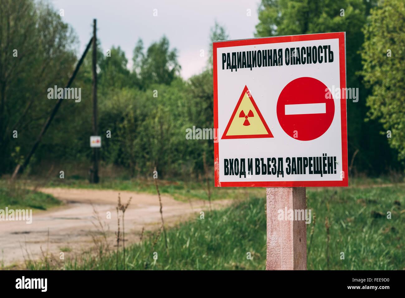 Ionizing radiation warning sign near the village in the Gomel region of Belarus. Radiation contamination area. - Stock Image