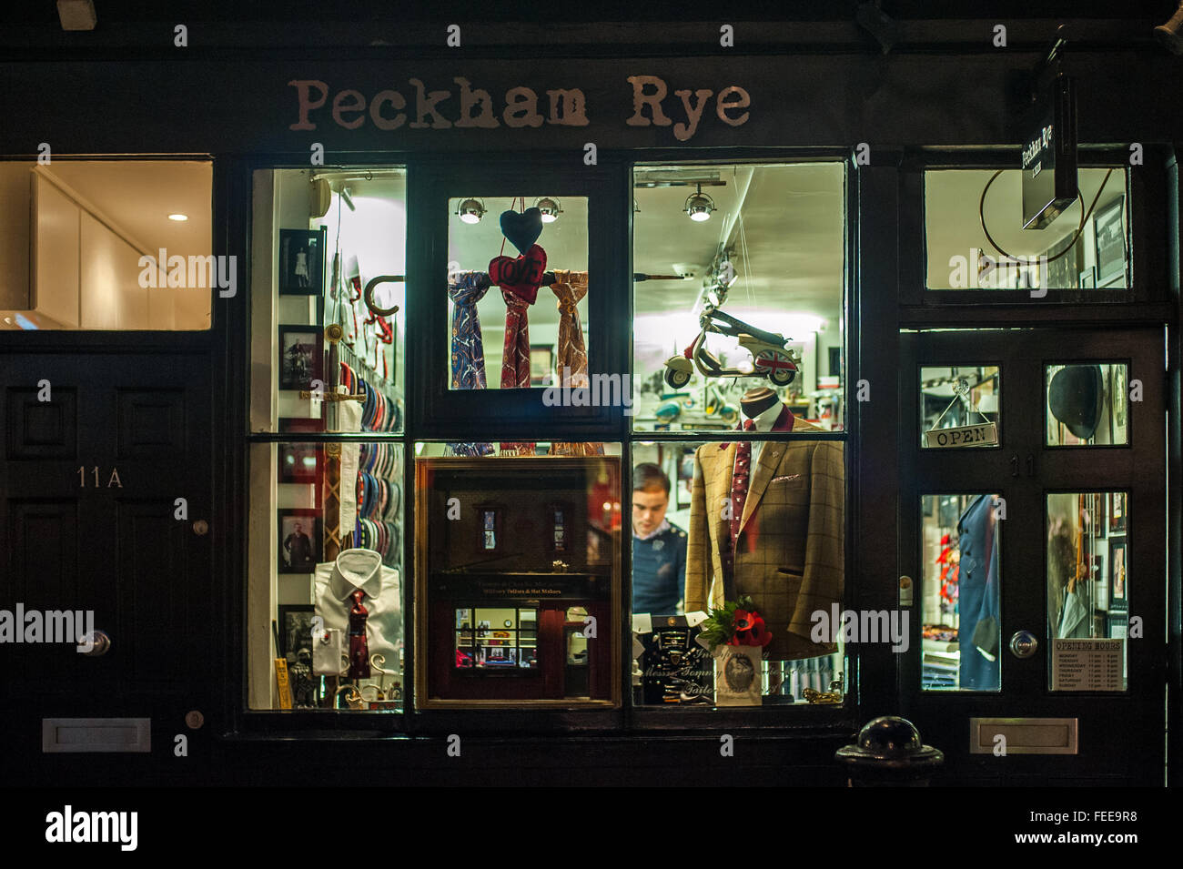 Outside a traditional suit and tie shop at night, Soho, London - Stock Image