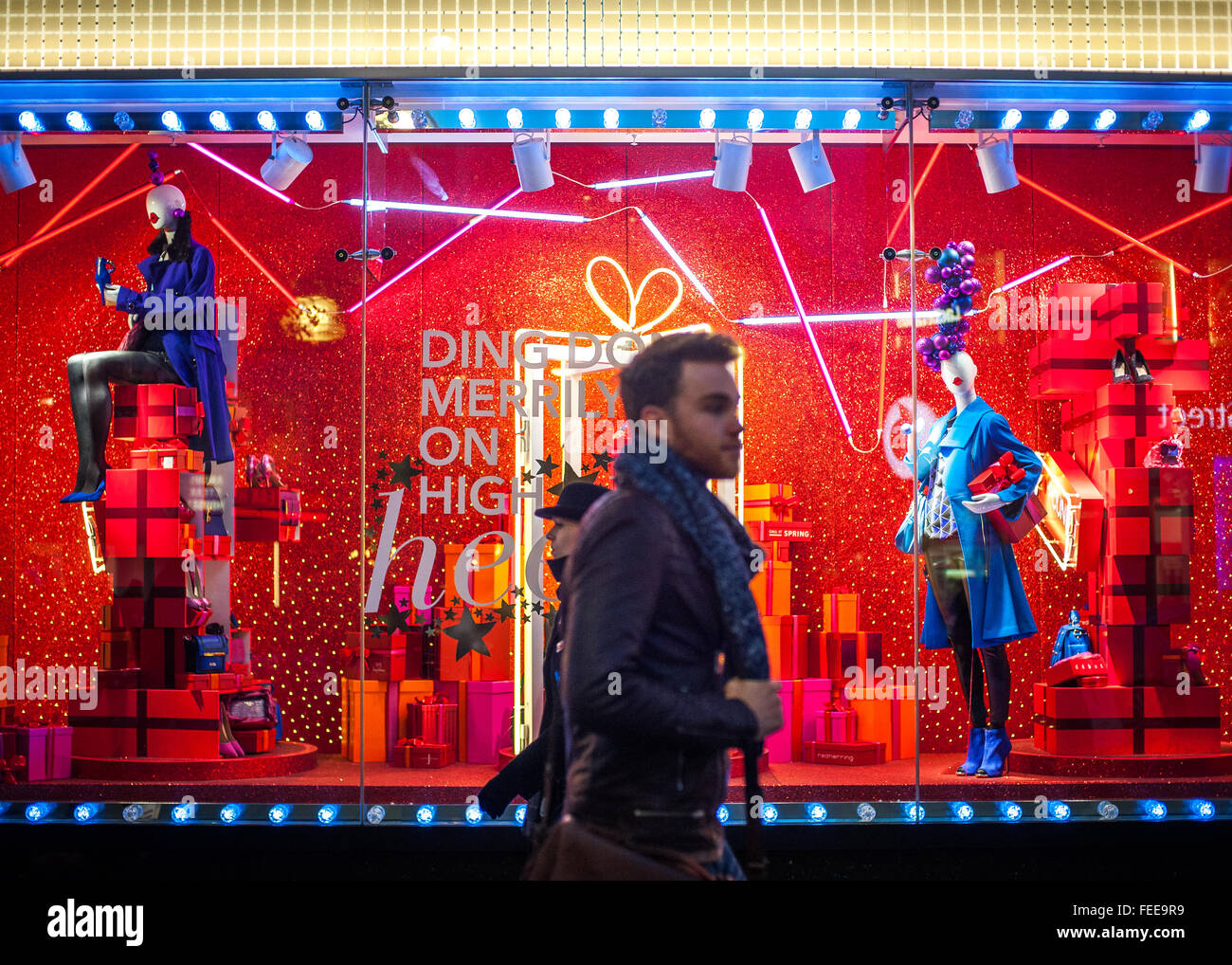 Christmas shoppers and window dressing in Oxford Street, London - Stock Image