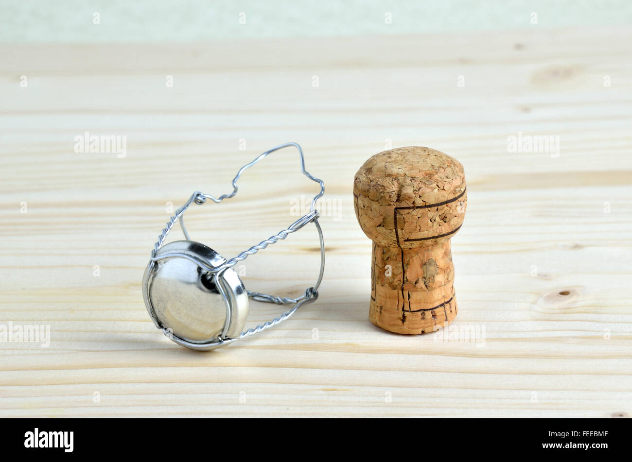 Champagne cork and wire retaining frame and cap on wooden table ...