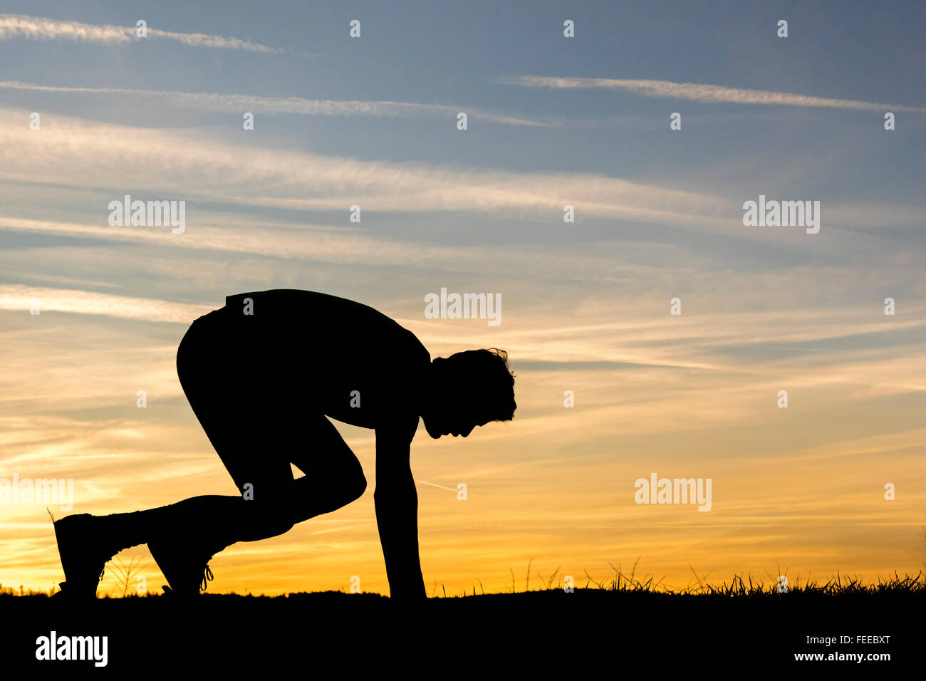 Silhouette, night sky, man crouching before sprint, athletics - Stock Image