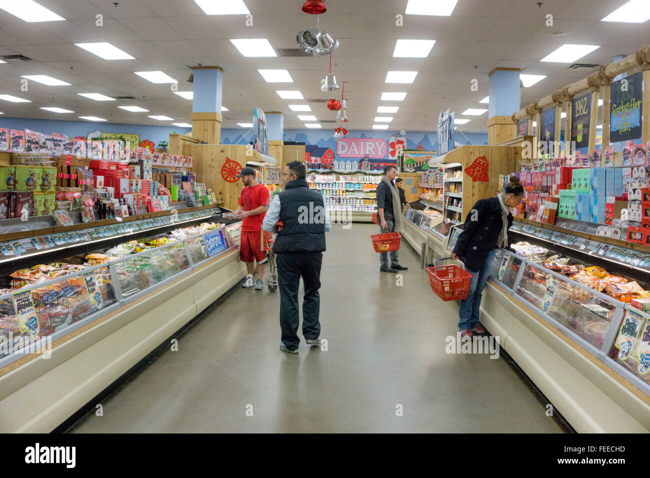 plenty of room for customers to browse in wide aisles of Trader Joes decorated for Christmas with hanging balls - Stock Image