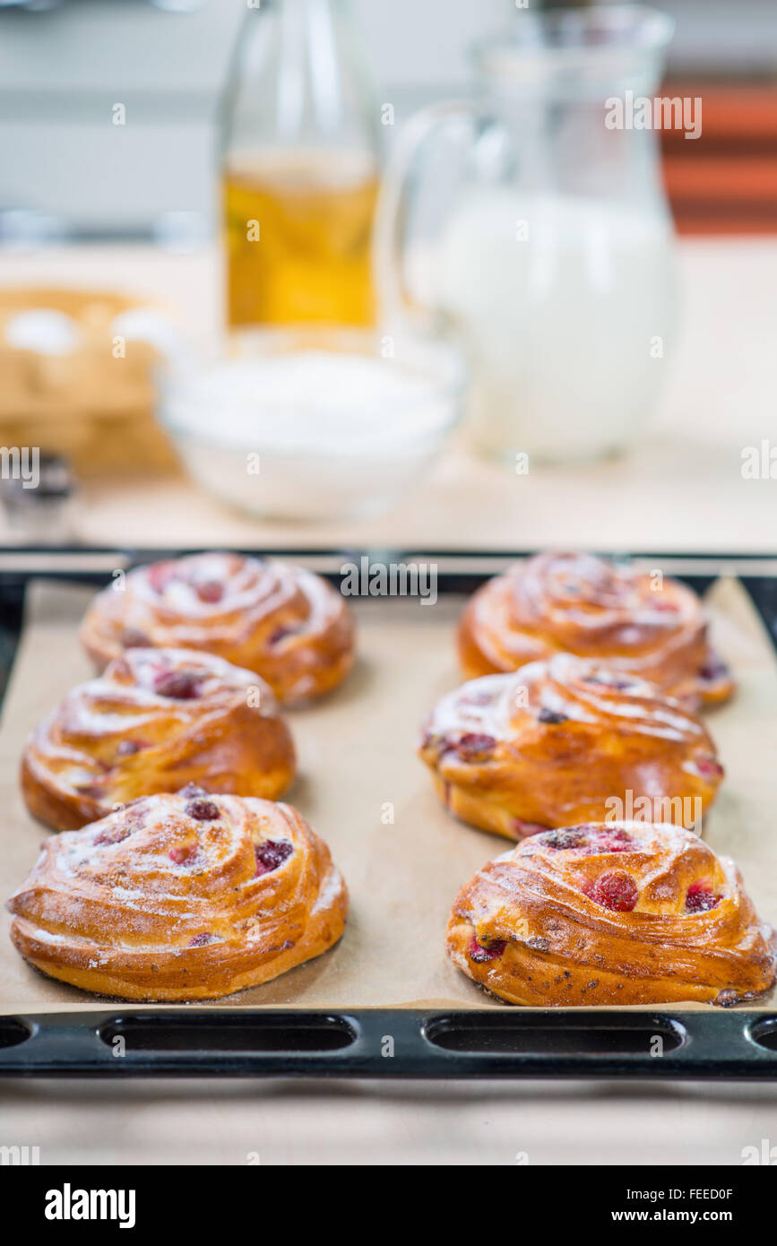 Baking tray with buns standing on the table - Stock Image