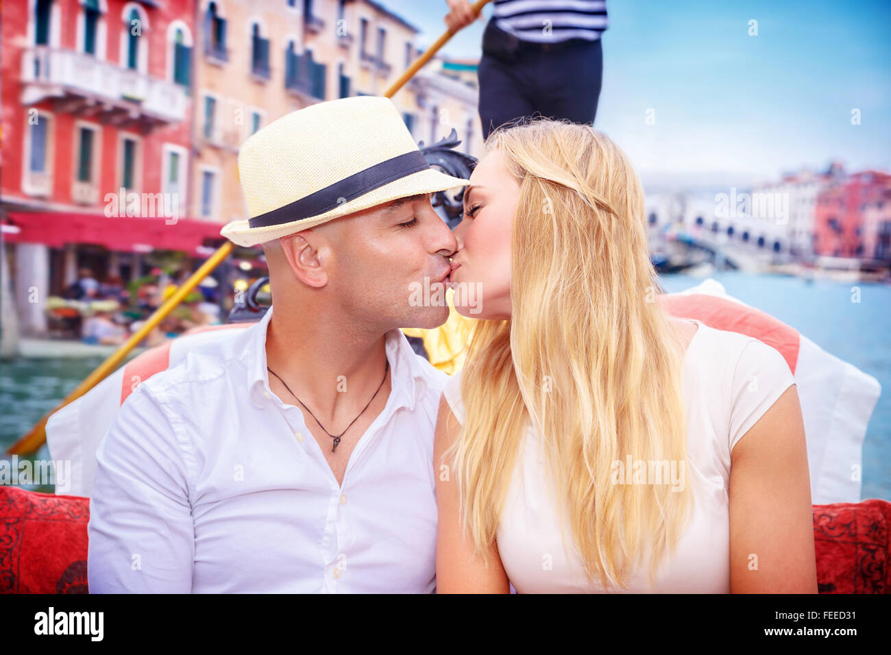 Portrait of happy loving couple in romantic honeymoon, kissing on a gondola, vacation in Italy, enjoying holidays - Stock Image