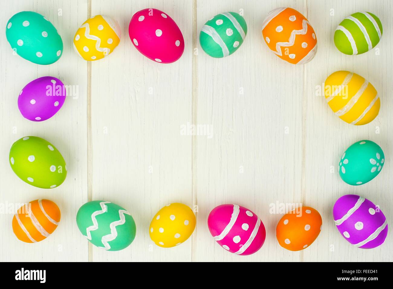 Colorful Easter egg frame against a white wood background Stock ...