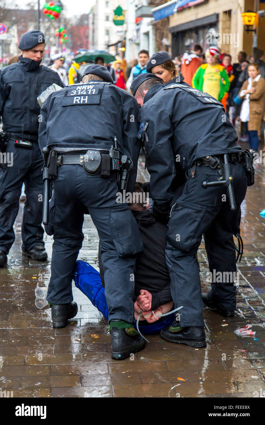 Police on duty during street carnival party in Cologne, Germany, on Shrove Thursday, arresting a drunken and violent Stock Photo