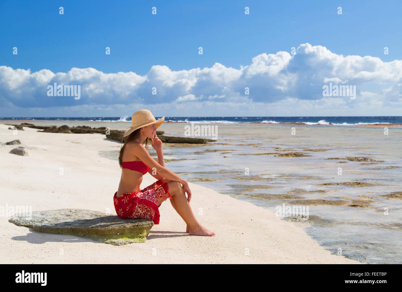 Woman sitting on beach, Fakarava, Tuamotu Islands, French Polynesia - Stock Image