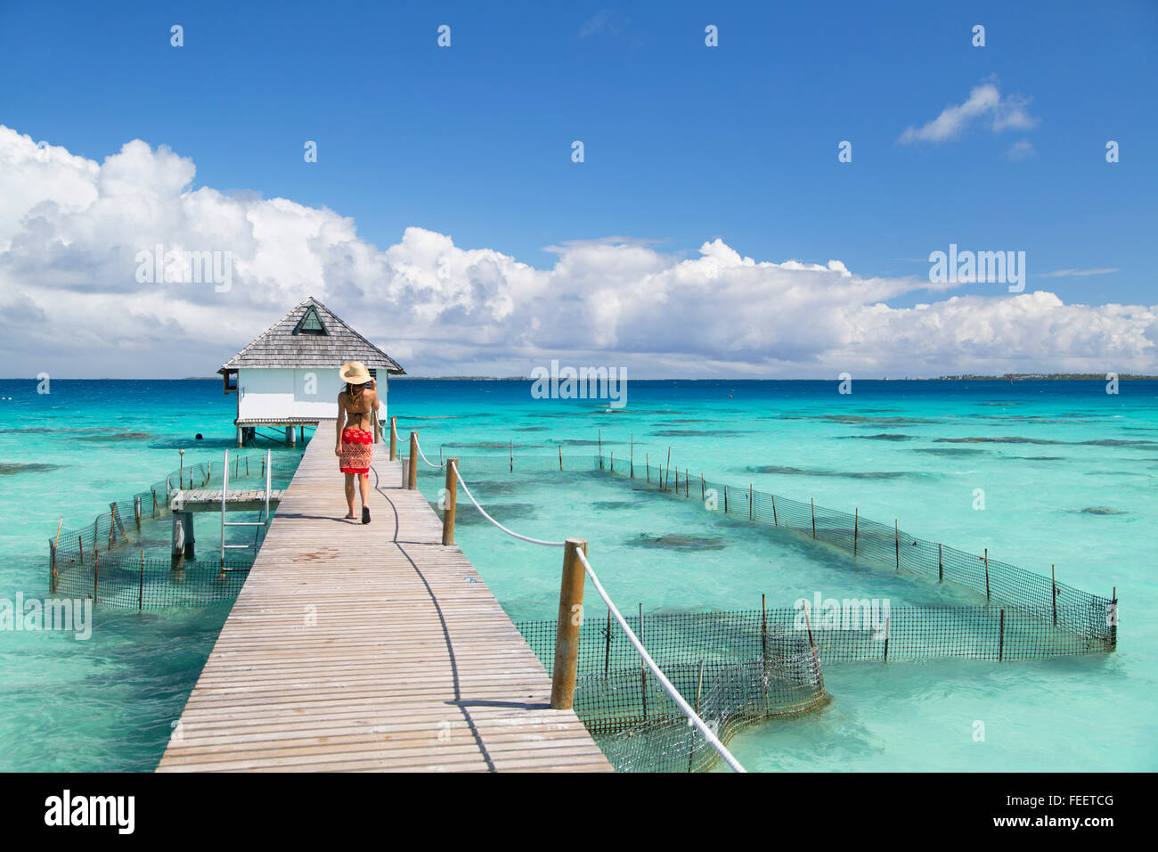 Woman walking on jetty, Fakarava, Tuamotu Islands, French Polynesia - Stock Image