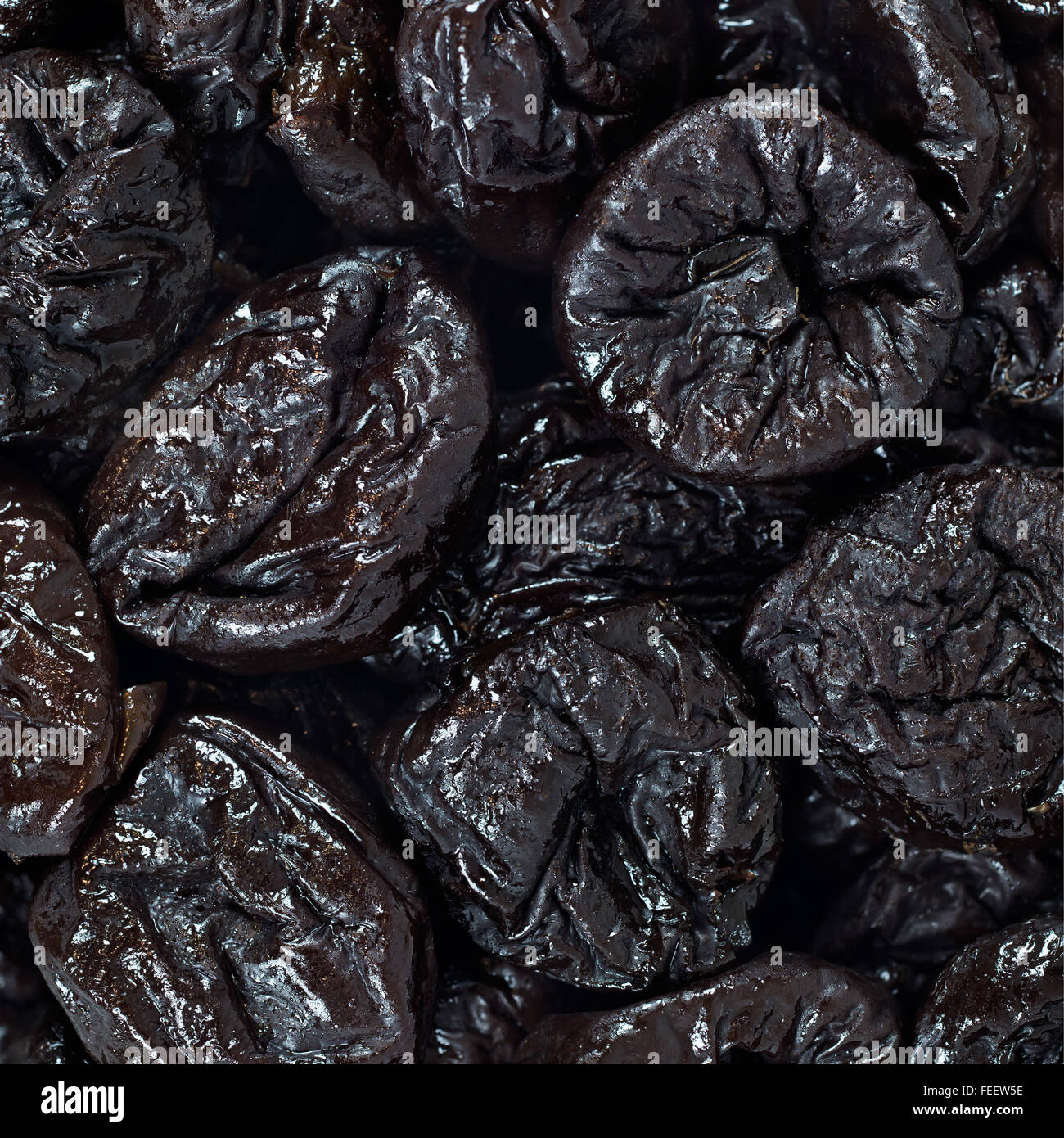 Dried plums or prunes fruit background texture pattern wallpaper - Stock Image