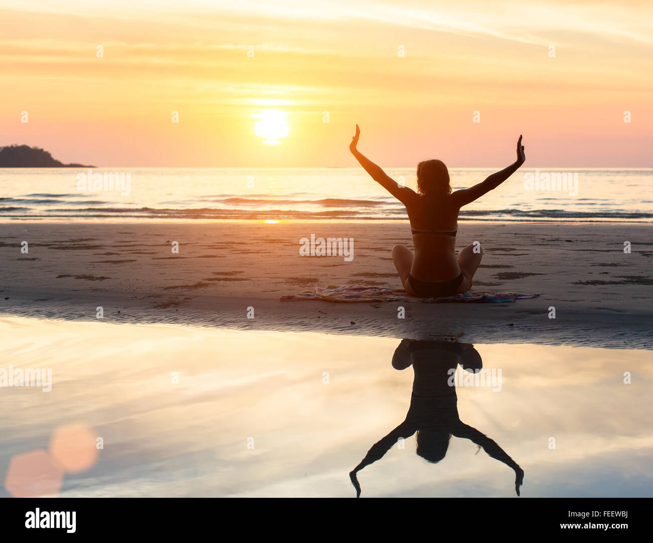 Yoga silhouette of woman doing exercise at sunset on the beach with reflection in the water. - Stock Image
