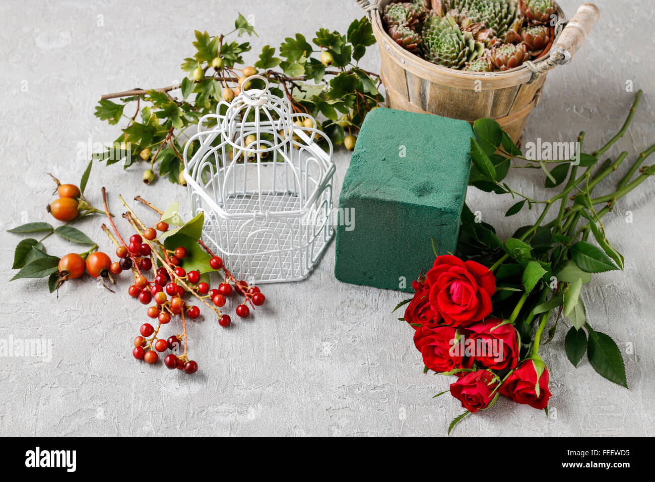 Florist at work: how to make floral arrangement with roses and hawthorn berries in vintage birdcage. - Stock Image