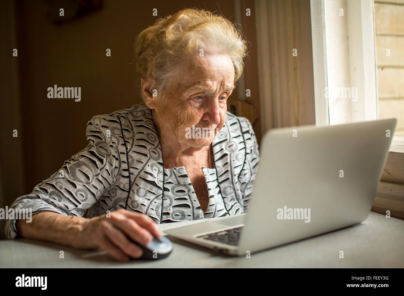 Elderly woman working on laptop at home sitting at the table. - Stock Image