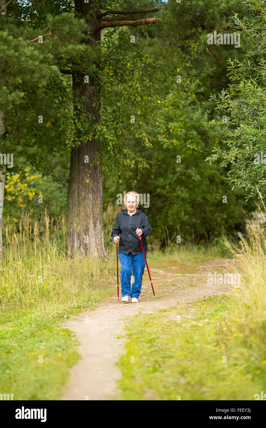 An elderly woman on a walk in the Park practicing Nordic walking. - Stock Image