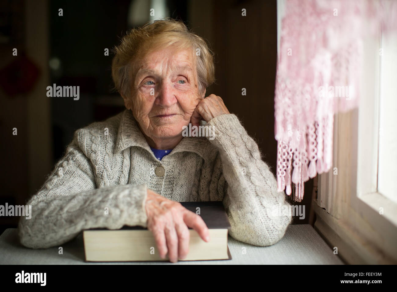 An elderly woman sits with a big book near the window. - Stock Image