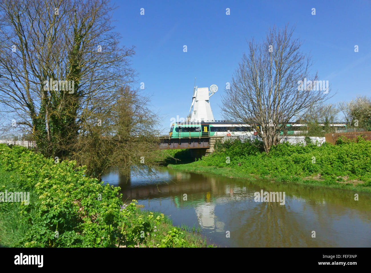 South East electric train crossing the bridge over the  river Tillingham  just outside Rye station by the windmill, Stock Photo
