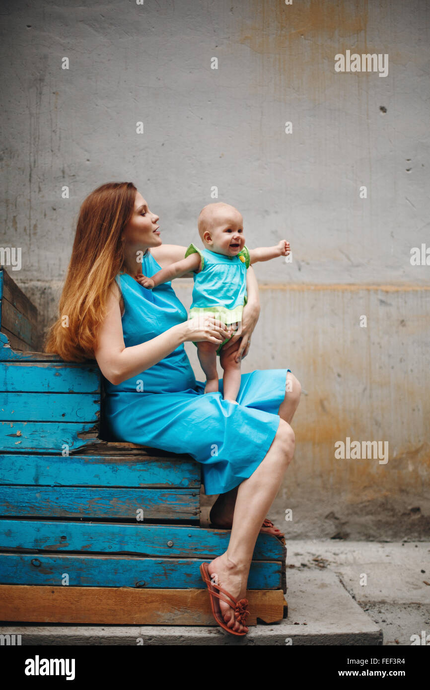 Cute 1 year Baby Standing on Mother`s Knees. Family Clothing Style with Blue Colors. Selective Focus on Mother. - Stock Image