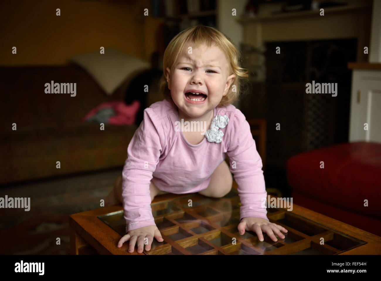 An unhappy eighteen month old baby with a temperature knelling on a side table in her home crying and looking unhappy. - Stock Image