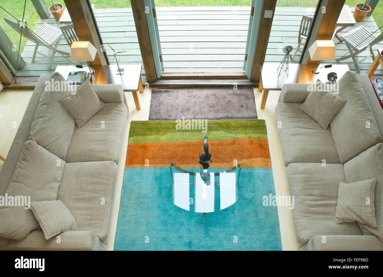 living room area, soft sofas, glazed doors onto deck. - Stock Image