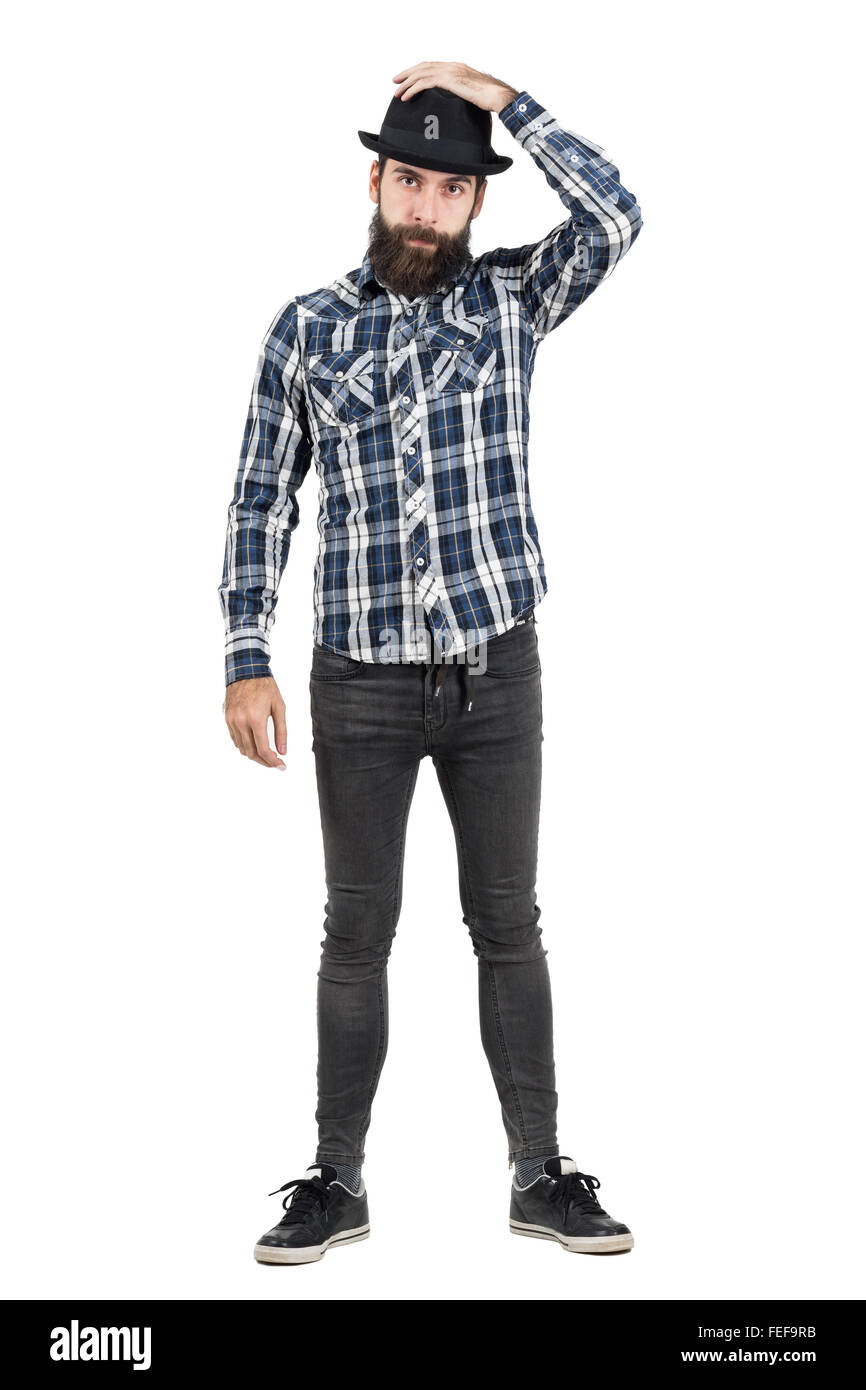 Bearded hipster putting on black fedora hat looking at camera. Full body length portrait isolated over white studio - Stock Image