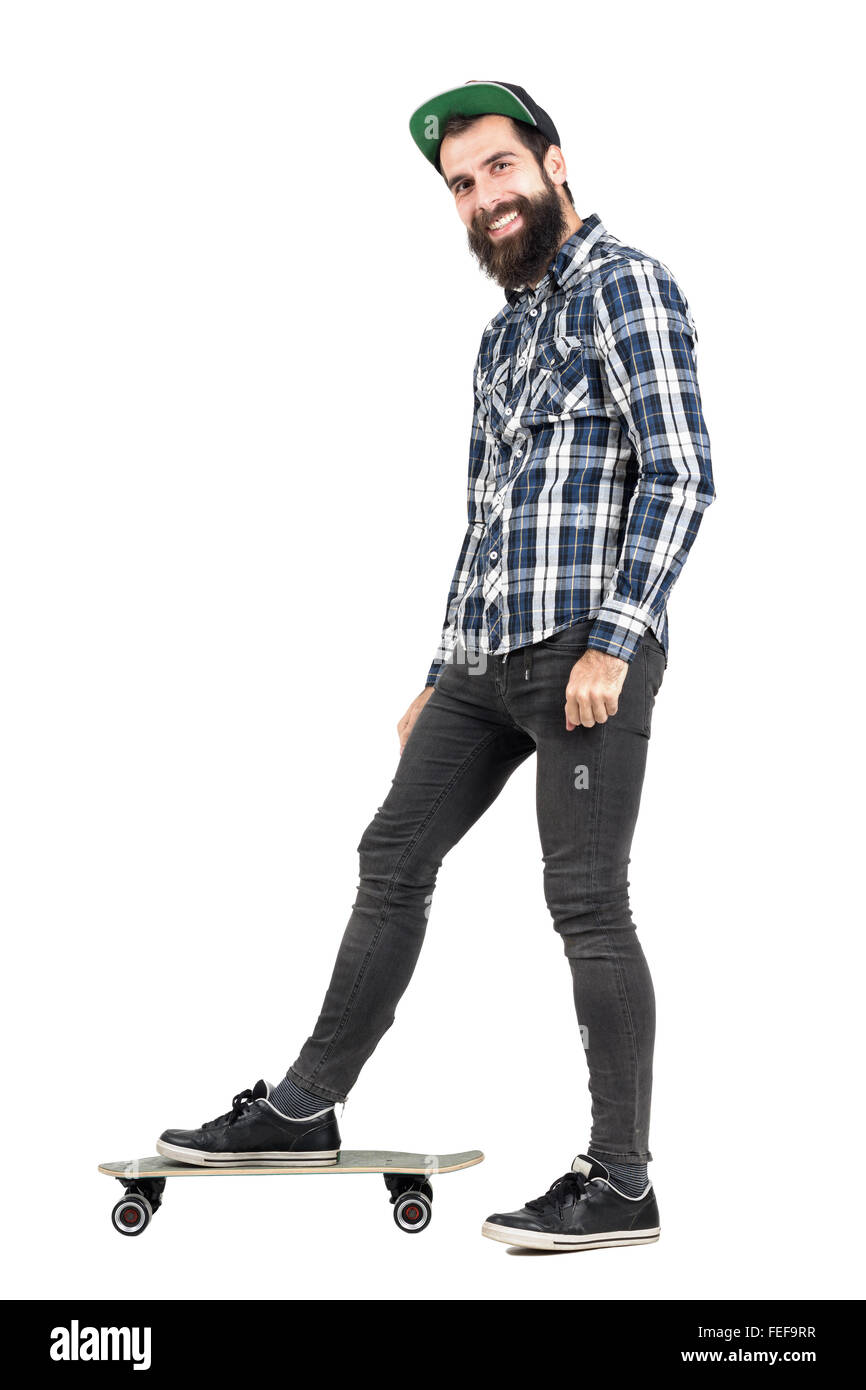 Laughing positive hipster with smiley piercing standing on skateboard side view. Full body length portrait isolated - Stock Image