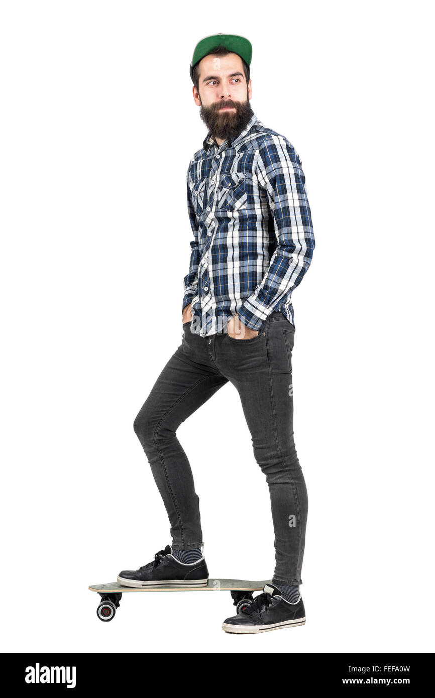 Happy confident hipster with hands in pocket wearing cap standing on longboard side view. Full body length portrait - Stock Image