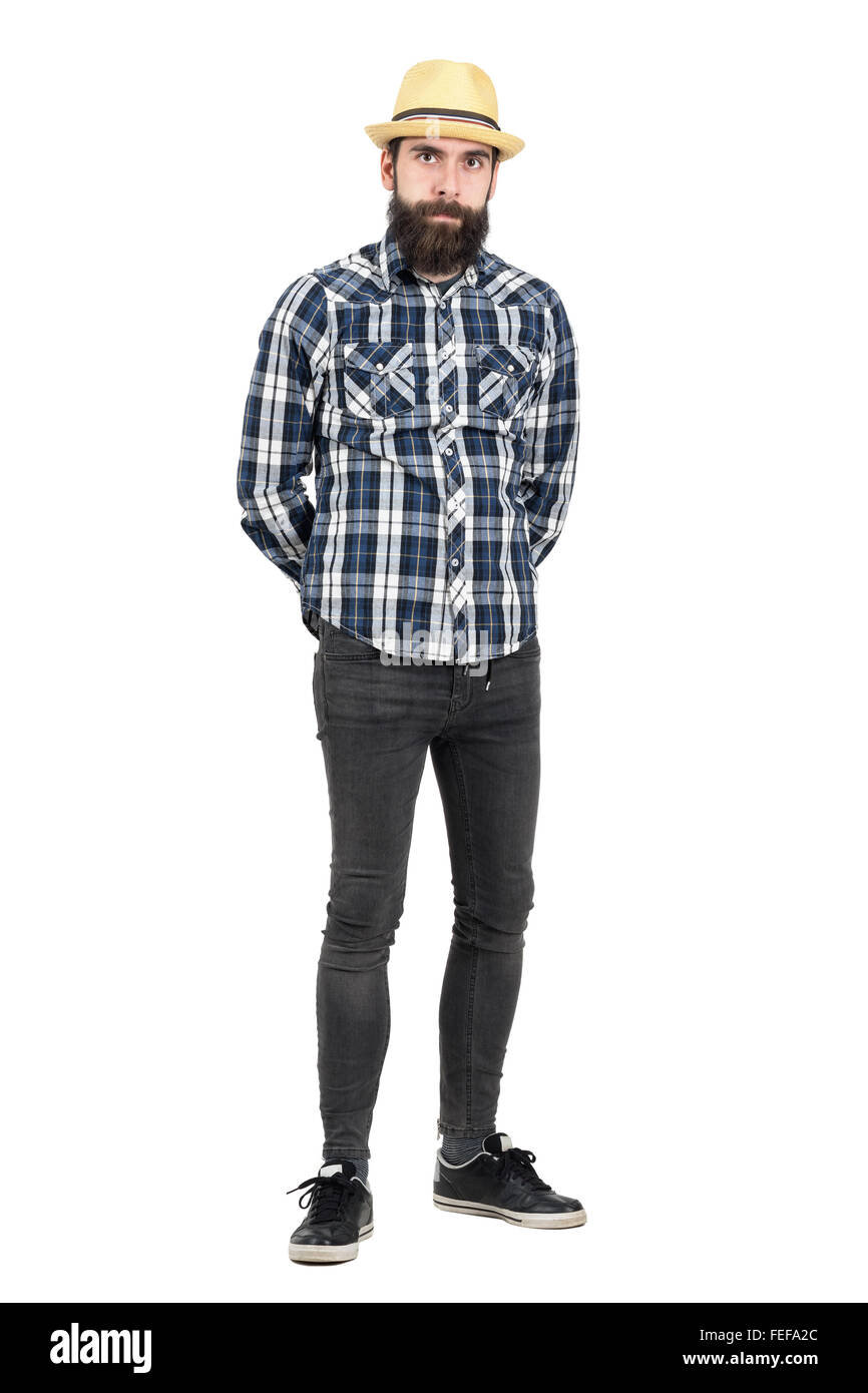 Serious hipster wearing straw hat with hands behind looking at camera. Full body length portrait isolated over white - Stock Image