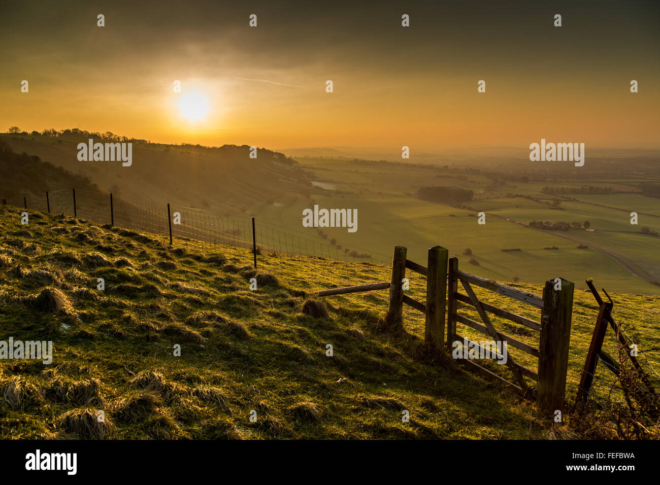 Public footpath & sunset over Wiltshire countryside near the town of Westbury from Bratton Camp and The Westbury Stock Photo