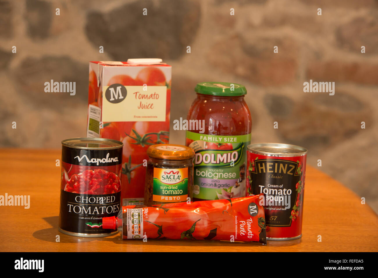 Group of tomato products including soup, puree, juice, sauce, pesto and chopped in cans,bottles, cartons and tubes. - Stock Image