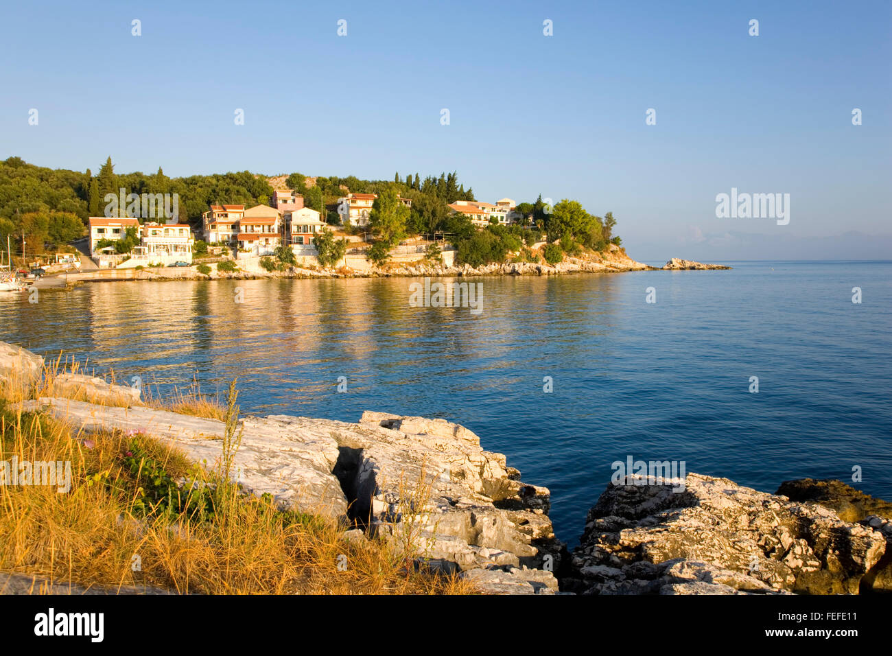 Kassiopi, Corfu, Ionian Islands, Greece. Rocky headland lit by the early morning sun. - Stock Image