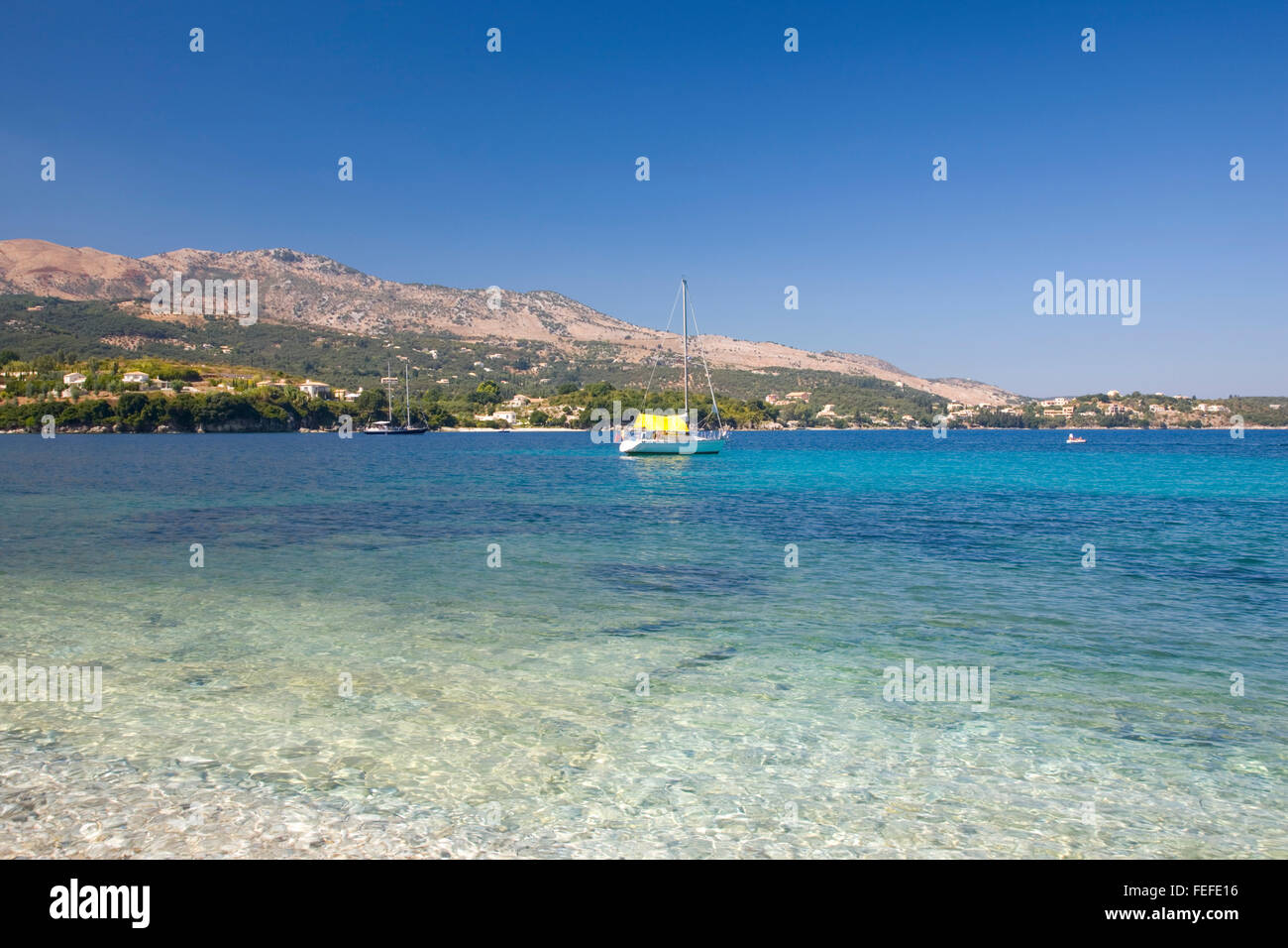 Kassiopi, Corfu, Ionian Islands, Greece. View across the clear turquoise waters of Avlaki Bay, yacht anchored offshore. - Stock Image