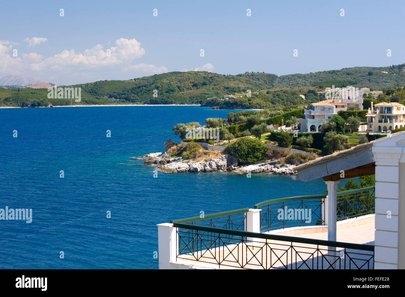 Kassiopi, Corfu, Ionian Islands, Greece. View over harbour entrance to the deep blue waters of Avlaki Bay. - Stock Image