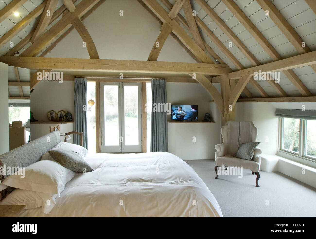 Master bedroom in barn conversion. Oak ceiling, french windows. New build - Stock Image