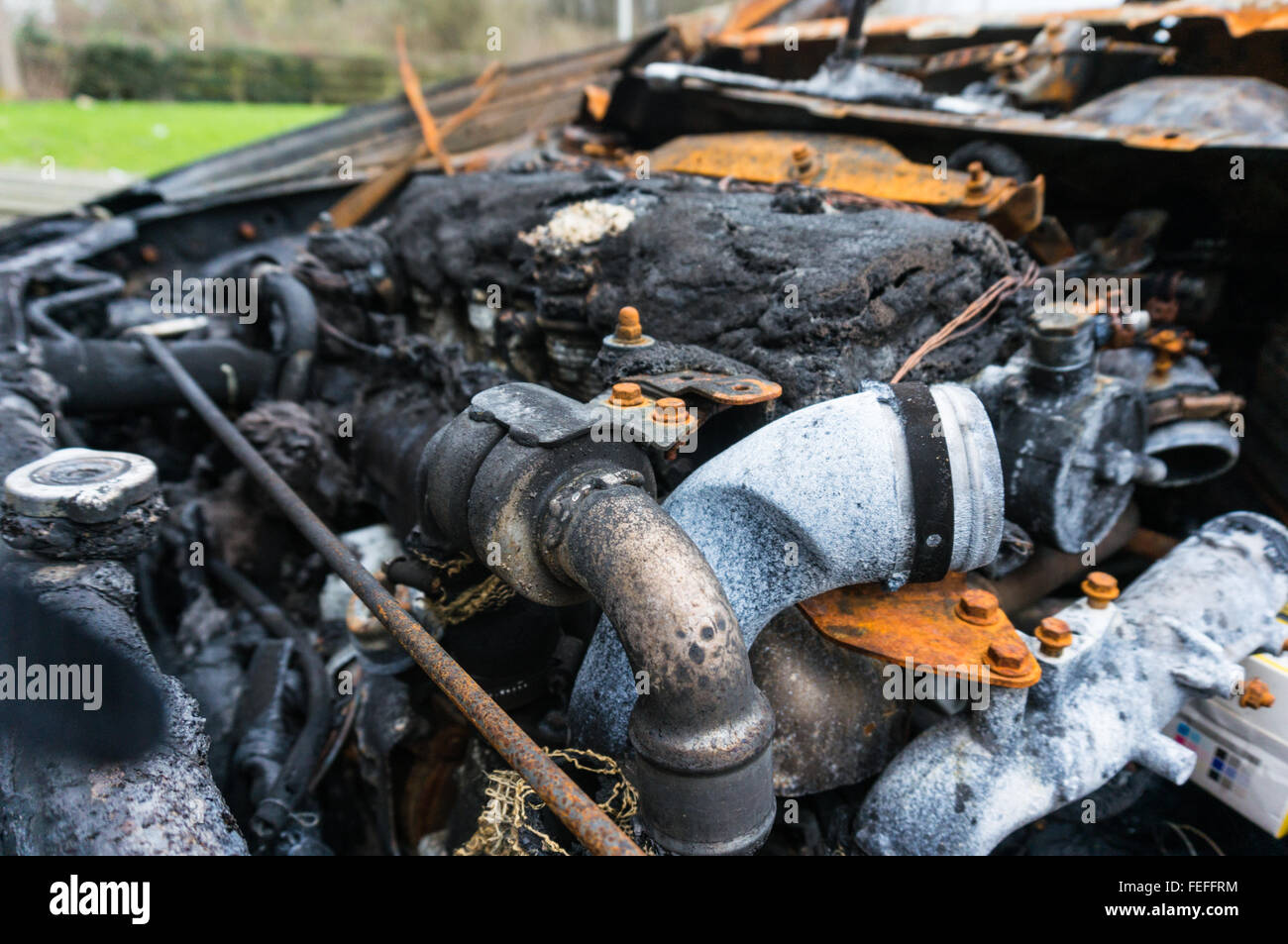 Engine compartment of abandoned fire damaged car - Stock Image