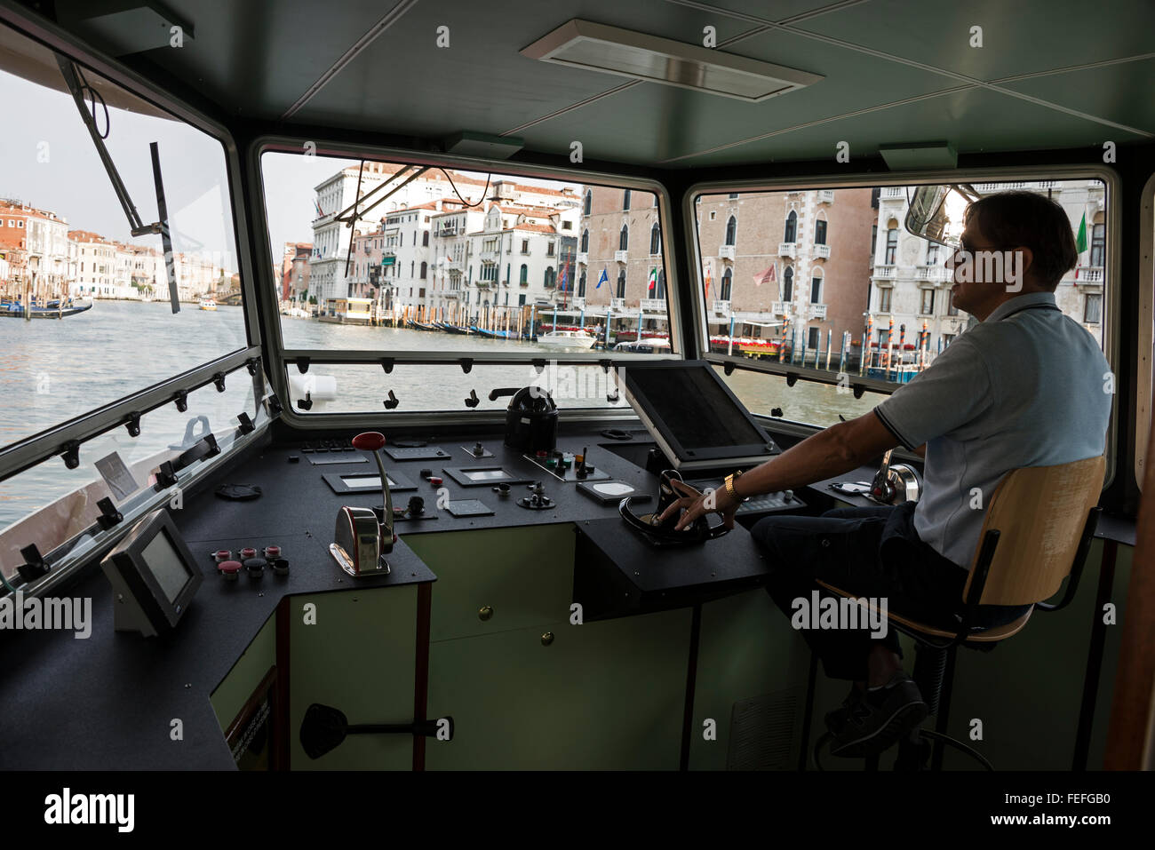 A crew member at the controls of the ACTV  vaporetto ( water bus)  operating on the Canal Grande ( Grand Canal) - Stock Image