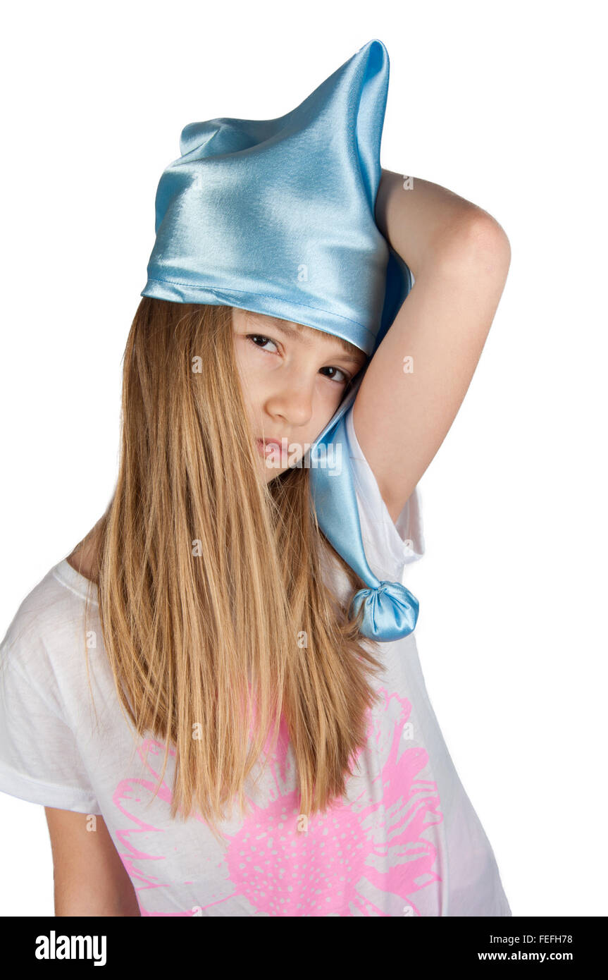 Cute girl in blue sleeping hat  stretching herself isolated on white - Stock Image