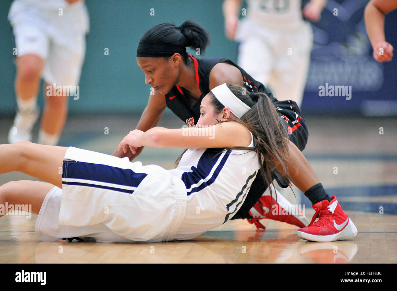 High school players fight  for the basketball and seek to claim possession during  a floor battle. USA. - Stock Image