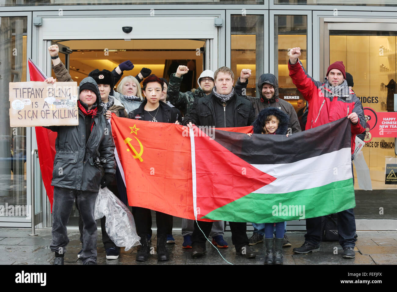 pro Palestinian campaigners standing with a Palestinian flag and a Communist party flag outside Selfridges in Manchester - Stock Image