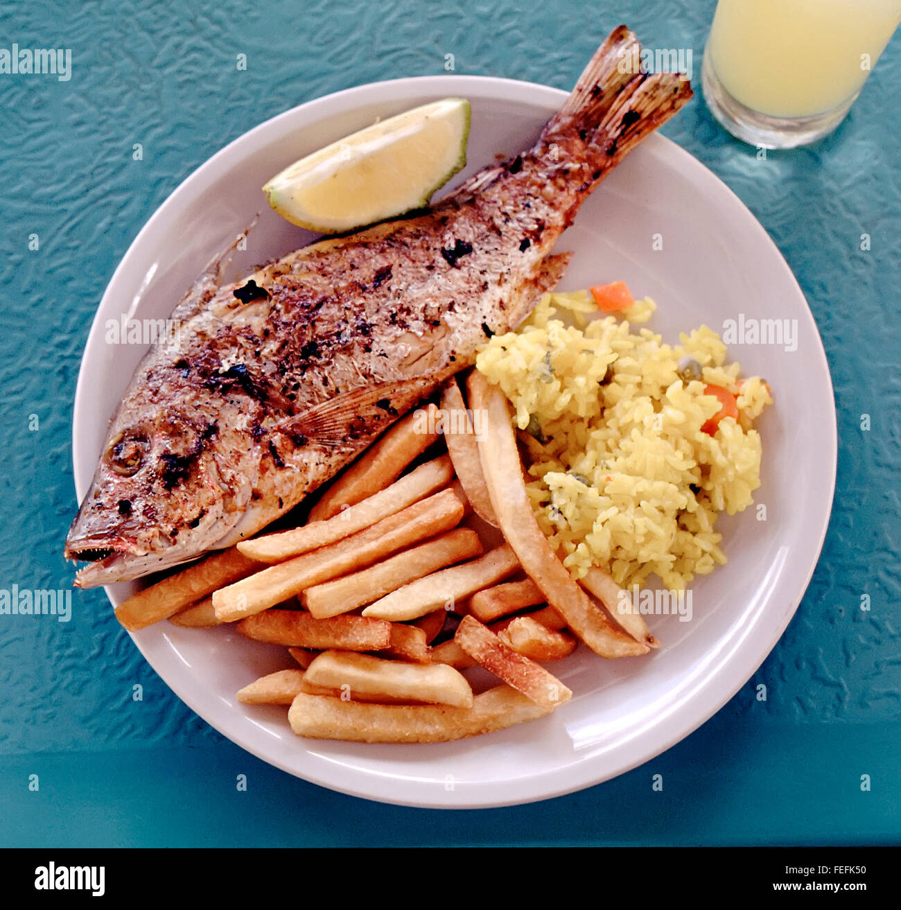 Fish and chips with rice and lemon, fresh caught grilled snapper, Caribean - Stock Image