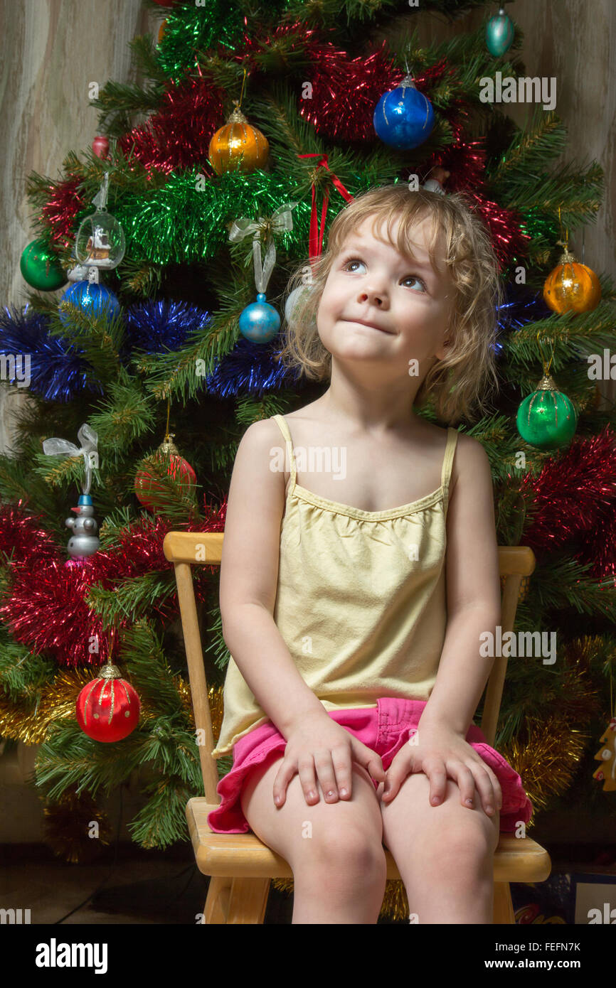 little girl dreamily looking up on a chair near the Christmas tree - Stock Image