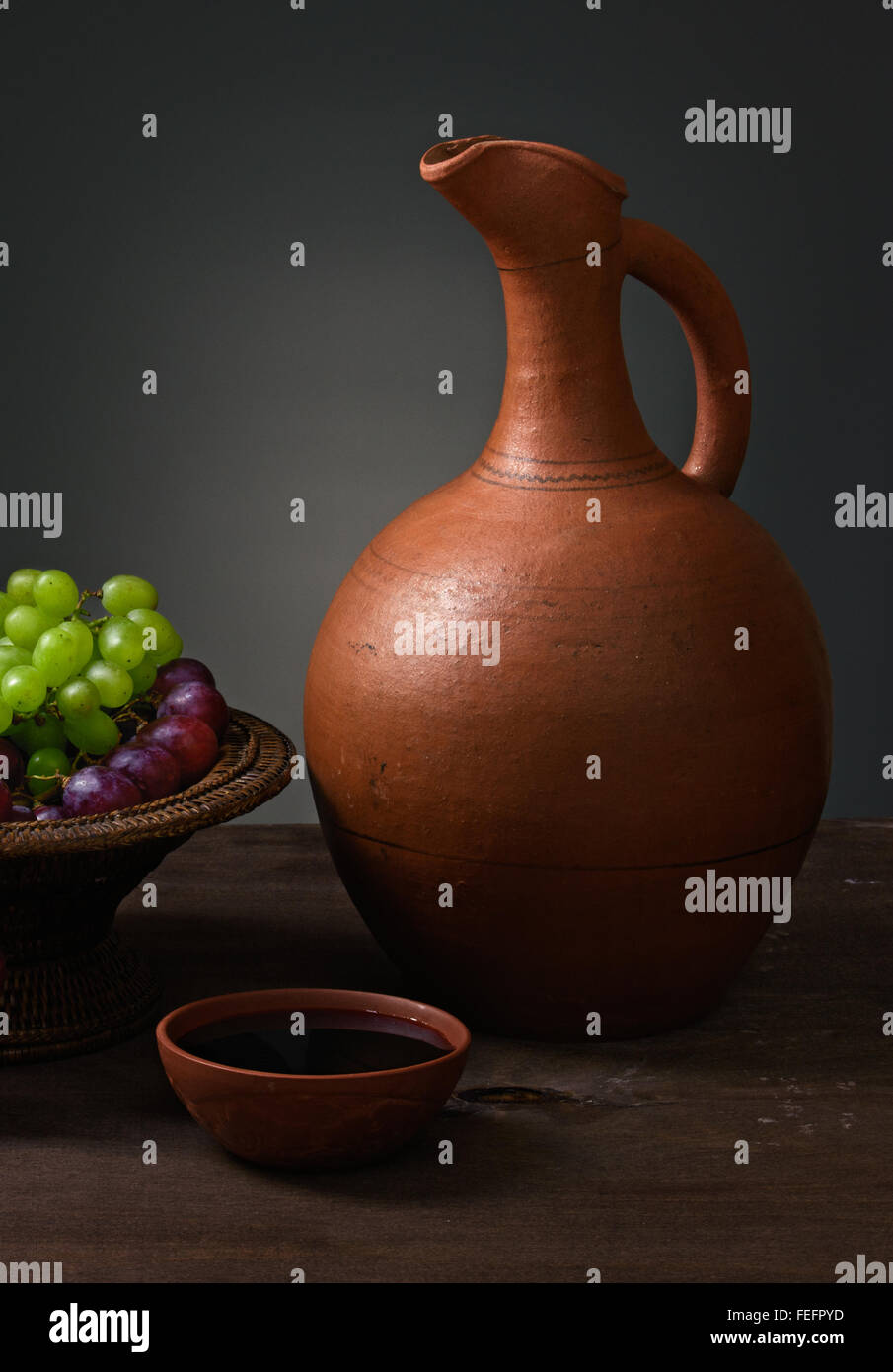 red wine with grapes and a pitcher on a wooden table - Stock Image