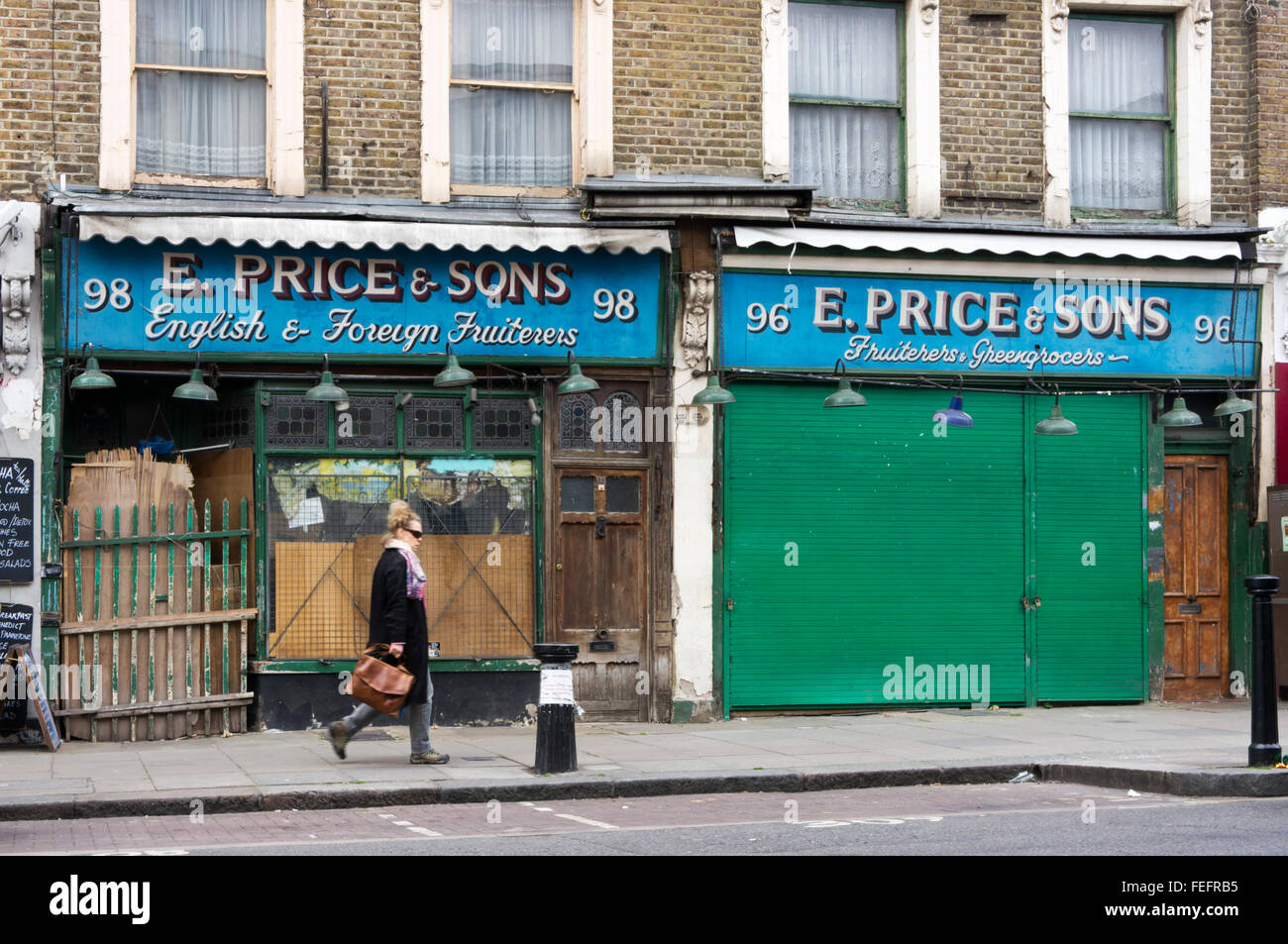 Woman (motion blurred) walking in front of closed greengrocers & fruiterers in Golborne Road. - Stock Image