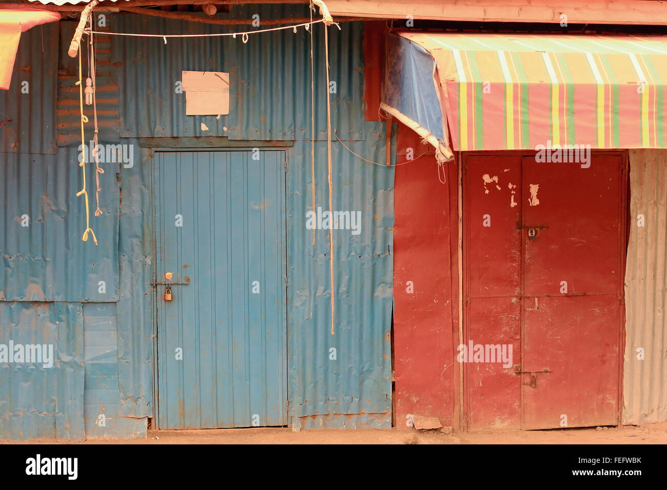 Tin doors painted blue and red of closed shops-area surrounding the Gebriel Bete-St.Gabriel christian church-Kombolcha-Ethiopia. & Tin doors painted blue and red of closed shops-area surrounding the ...