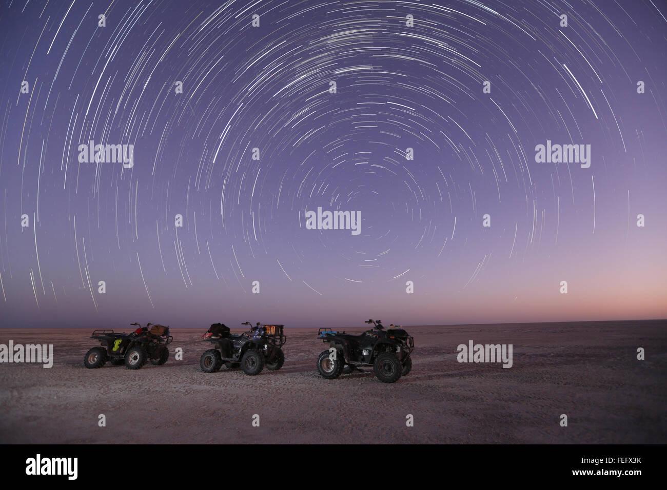 Quad bikes under a star trail. - Stock Image