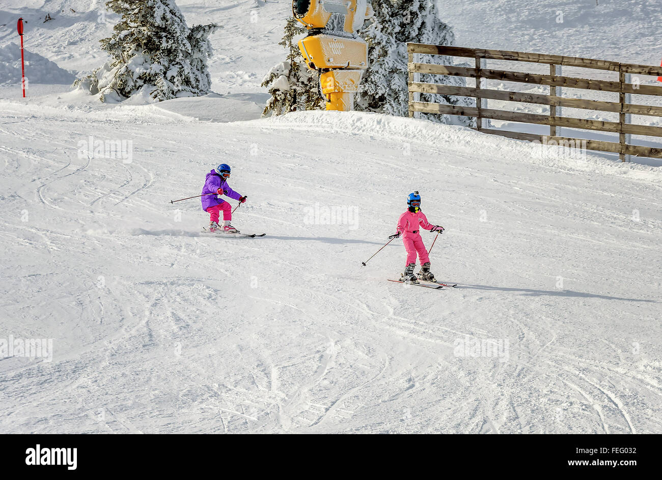 Two Little girls skiing fast downhill - Stock Image