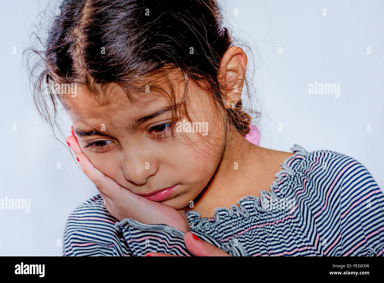Little girl with toothache in white background - Stock Image