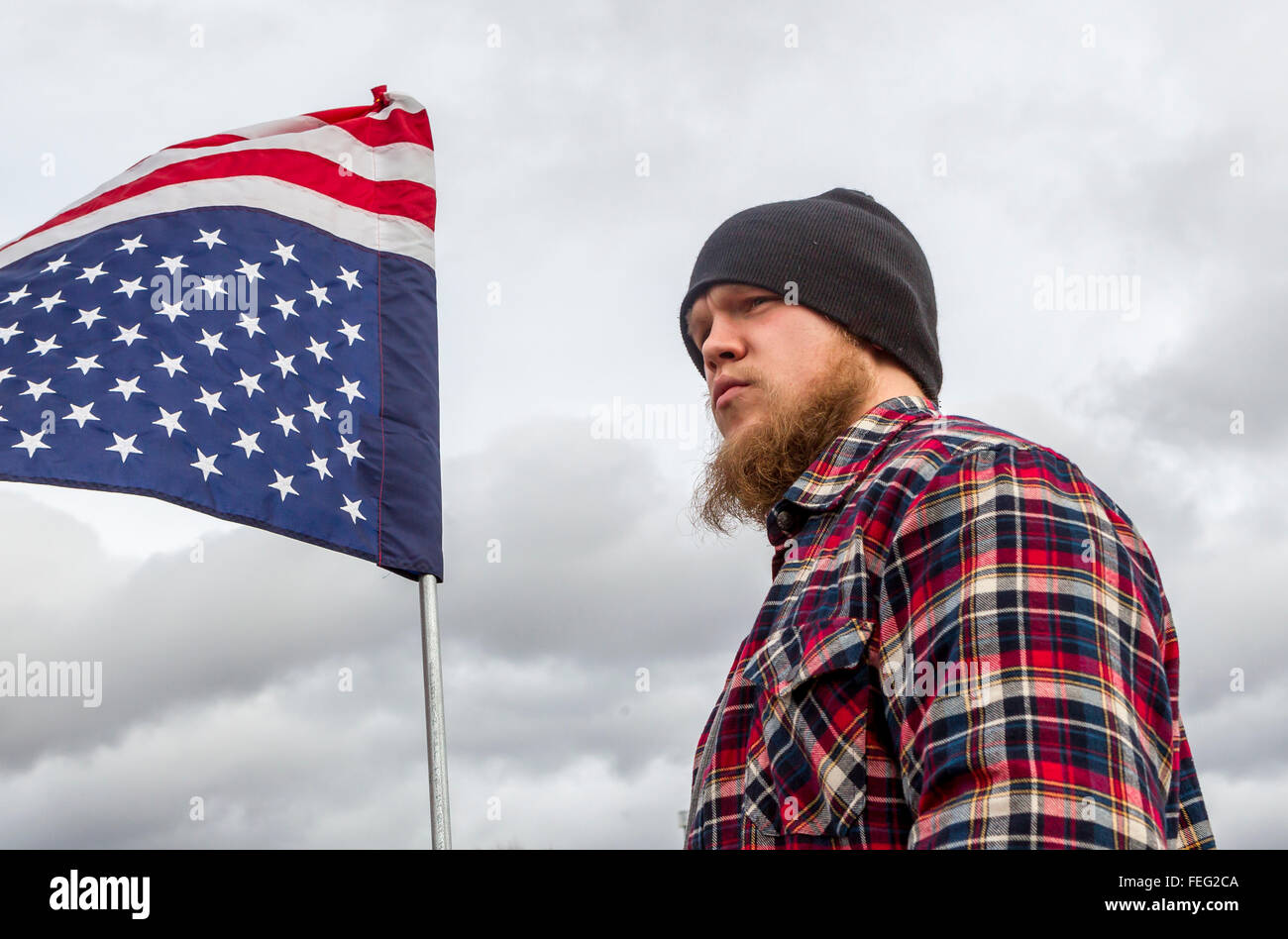 Young man holds upside down flag. - Stock Image