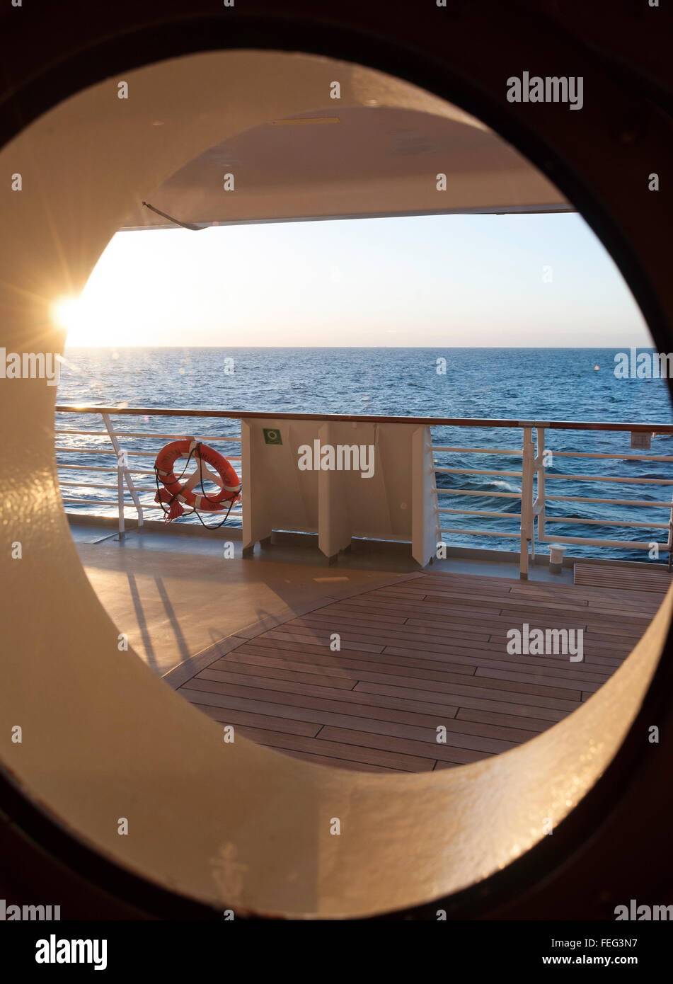 View of sea at sunset through port hole of Royal Caribbean's 'Brilliance of the Seas' cruise ship, North - Stock Image