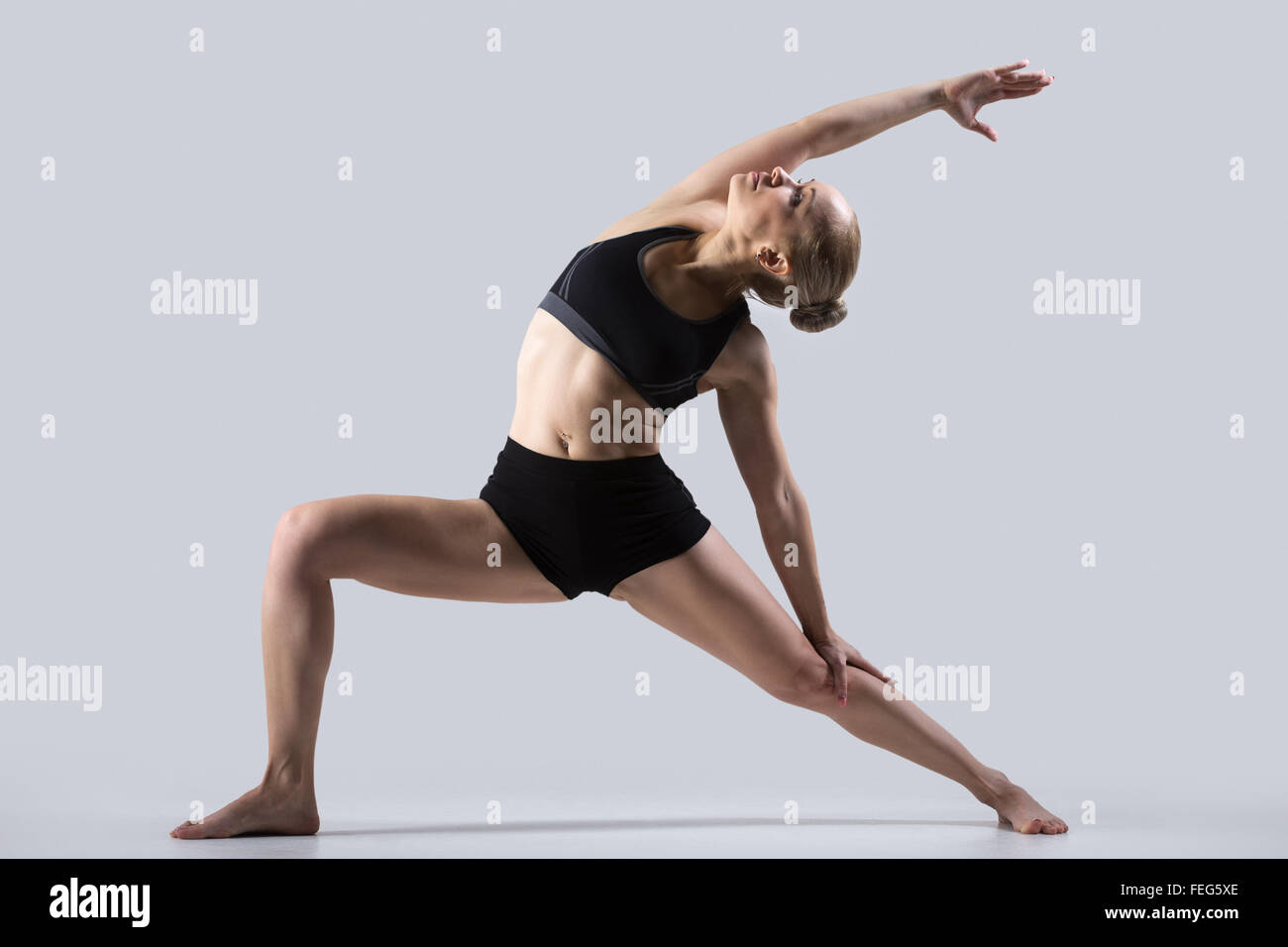 Sporty beautiful young woman practicing yoga, doing high lunge exercise, Reverse Warrior Pose, Viparita Virabhadrasana, - Stock Image